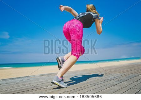Female athlete in starting position ready for running. Young woman ready for sports exercise on beach