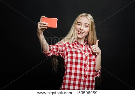 Fooling around . Amused playful cheerful teenager expressing positivity and using modern gadget while taking selfie and standing against black background
