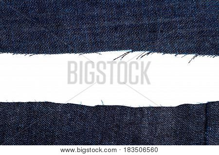Pieces of dark blue jeans fabric isolated on white background. Rough uneven edges.