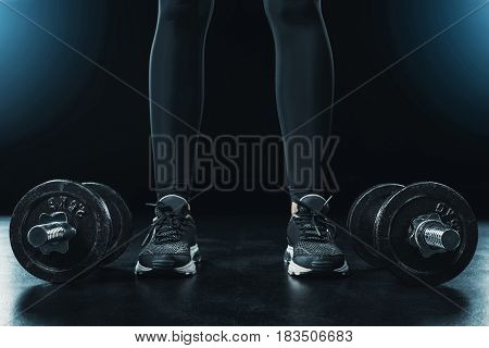 Low Section Of Sportswoman Standing Near Dumbbells Isolated On Black.