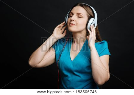In the world of tunes. Young positive glad woman feeling peaceful and using headphones while enjoying the music and standing against black background