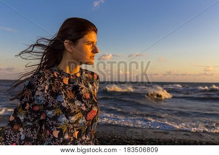 Young beautiful long hair woman on windy seashore at sunset