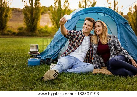 Shot of a happy couple camping on the nature and making a selfie
