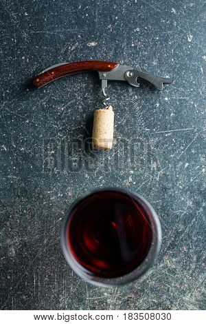 Corkscrew and red wine on old table.