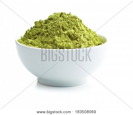 Green matcha tea powder in bowl isolated on white background.