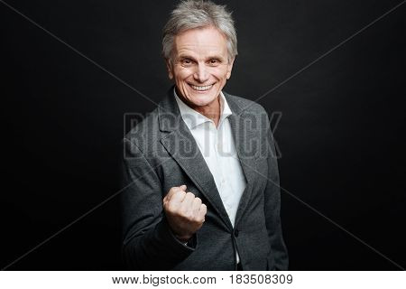 Facing difficulties with smile . Charming positive aged man expressing positivity and gesticulating while showing fist and standing against black background
