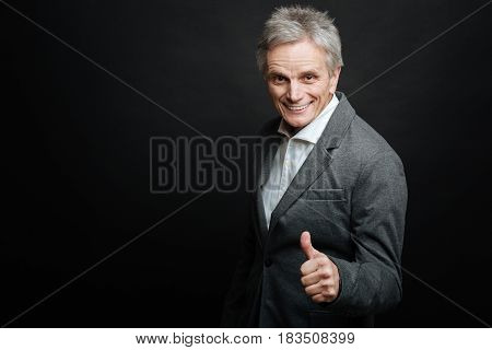 Always in happy mood. Charismatic optimistic senior man expressing joy and showing thumb up while standing isolated in black background