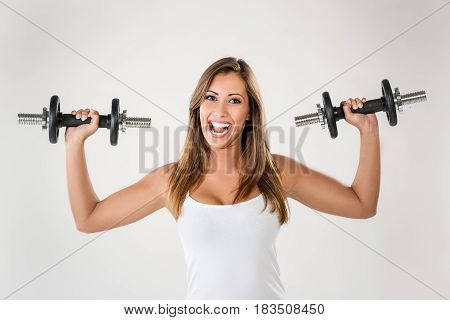 Beautiful young cheerful woman doing exercise to strengthen shoulder with dumbbells. Looking at camera.