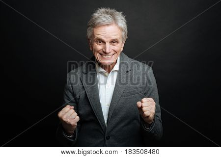 Celebrating success . Amused happy retired man expressing happiness and showing fists while smiling and standing isolated in black background