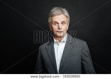 Feeling of puzzlement. Frustrated shocked aging man expressing astonishment and looking with wonder while standing isolated in black background