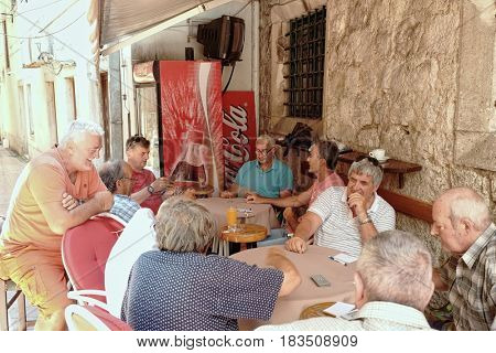KOTOR OLD TOWN, MONTENEGRO - JULY 19, 2016: middle age people are playing cards in a bar of a backstreet in Kotor Old Town