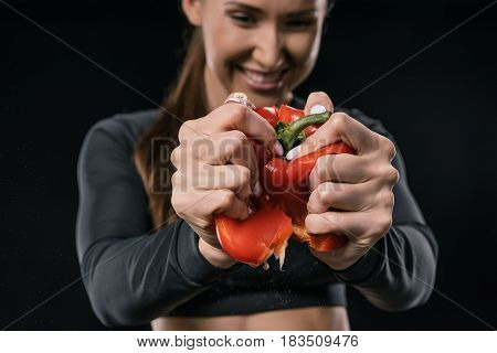Smiling Young Fitness Woman Squeezing Pepper In Hands Isolated On Black