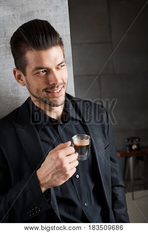Young handsome businessman drinking coffee, looking away. Copyspace for text.