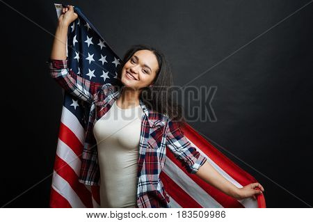 Lets talk about citizenship. Amused happy Hispanic American woman amusing and smiling while holding American symbol and standing isolated against black background