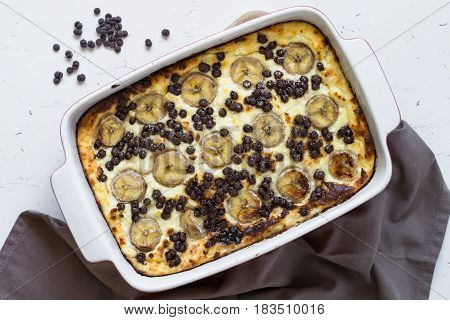 Cottage cheese casserole with banana and chocolate drops. Healthy breakfast or snack. Top view.