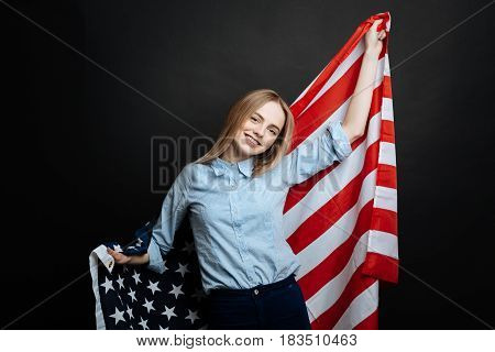 Enjoying patriotism. Proud cheerful happy girl having fun and smiling while holding national flag and standing isolated in black background