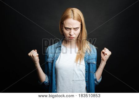 Tying to scare with my power . Furious irritated young woman expressing rage and showing fists while looking with anger and standing against black background