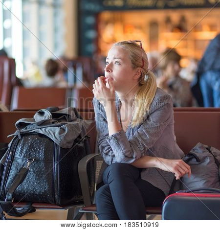Young blond caucsian woman waiting on airport terminal full of passenegers for her flight to depart.