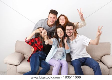 Home party. Friends having fun, taking selfie and posing to camera, sitting on couch indoors