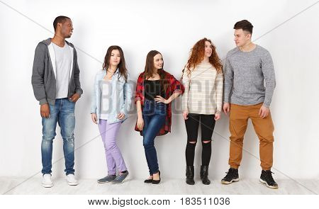 Education concept. Group of diverse students in casual outfits standing in line on white studio background