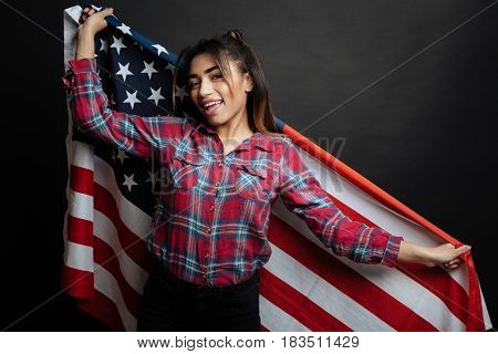 Representing my country and state . Amused charming Hispanic American woman amusing and expressing joy while holding American flag and standing against black background