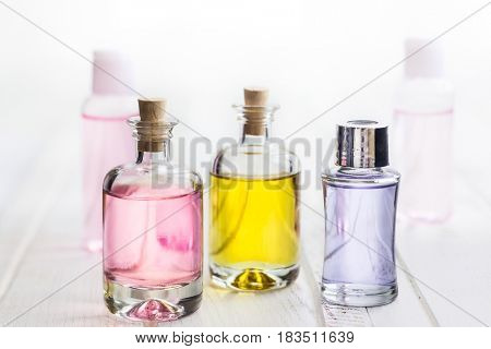 Bottles with essential aroma oil on white wooden background.Healthy skin care. Place for text.