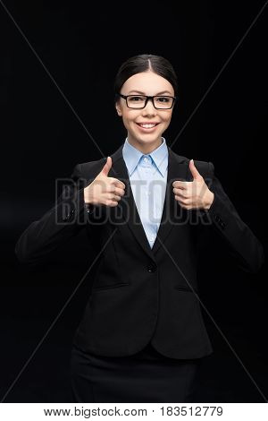 Brunette Businesswoman In Black Suit Showing Thumbs Up Isolated On Black