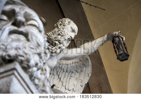 BOLOGNA,ITALY-DECEMBER 12,2016:Old statue on a tomb inside the monumental cemetery of the Certosa di Bologna during a sunny day.