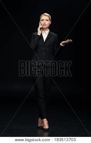 Confused Businesswoman Talking On Smartphone Isolated On Black