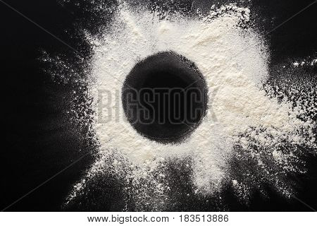 Abstract background. Sprinkled wheat flour circle, round spot on black. Top view on blackboard. Baking concept, cooking dough or pastry.