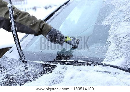 man is scraping a wind screen of a car