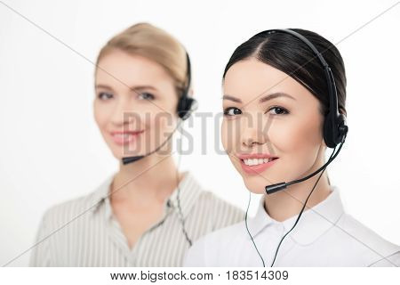Smiling Call Center Operators In Headsets Isolated On White, Focus On Foreground