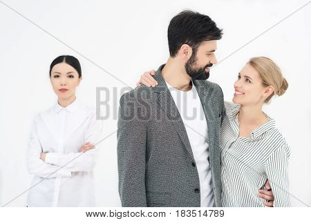Couple Looking At Each Other With Displeased  Friend Near By Isolated On White