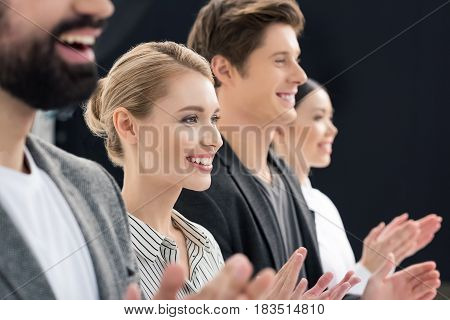 Group Of Smiling Business People Standing In Row Isolated On Black