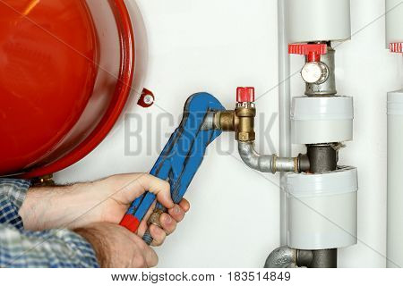 attaching a valve on a pipe in heating room