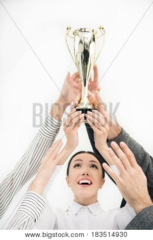 Businesswoman Looking At Goblet In Colleagues Hands Isolated On White, Business Teamwork Concept