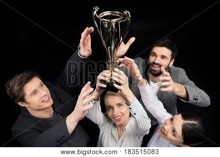 Happy Business People Holding Goblet Isolated On Black, Business Teamwork Concept