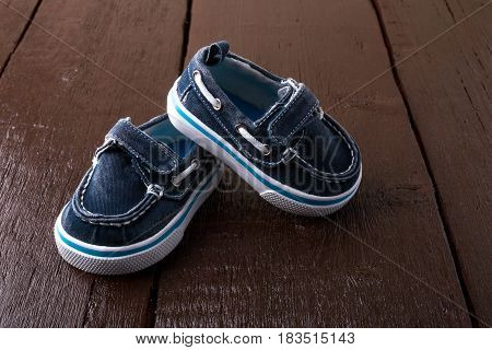 Blue Boat Shoes On Brown Wooden Background. Boy Footwear