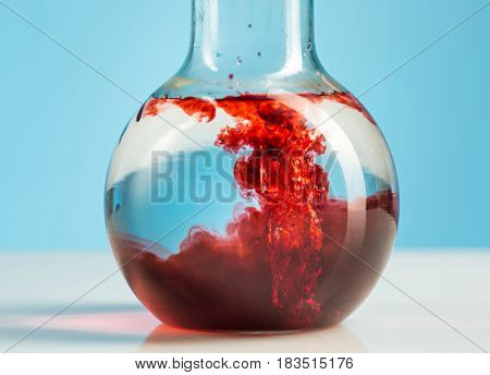 The laboratory glassware and red liquid inside on white background