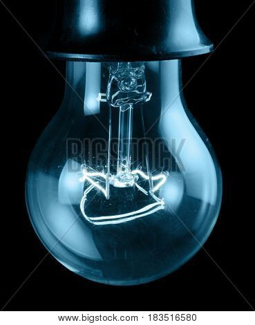 luminescent incandescent electric lamp in receptacle isolated on black background