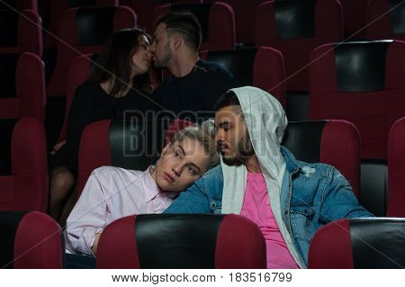 Group of young european adults watching movie in theater. Happy romantic couples in film session. Couple in love foreground sitting and hugging while another two kissing. Cinema, entertainment and leisure concept.