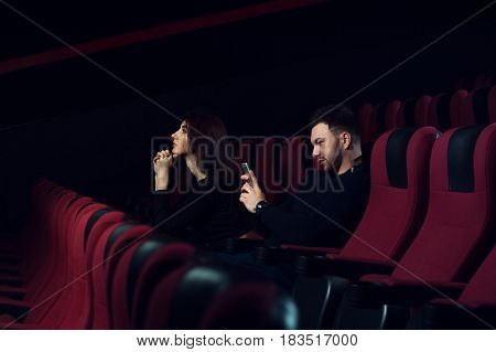 Young caucasian couple sitting in empty cinema theater. Man messaging with another person, while his girlfriend watching movie. Infidelity concept.