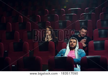 Young adults watching boring film in movie theater. Two friends looking at screen while another one using his smartphone. Cinema, entertainment and leisure concept.