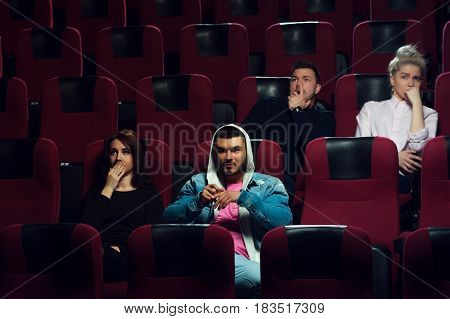 Young scared adults watching horror movie in cinema theater. Cinema, entertainment and leisure concept.