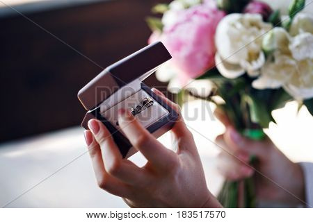Two wedding rings in infinity sign. Love concept. the wedding of two sisters twins. holding a box.