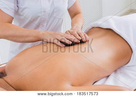 Black marble stone back massage in spa. Female beautician doctor with patient in wellness center. Professional massagist make relaxation procedure to beautiful indian girl in beauty parlor.