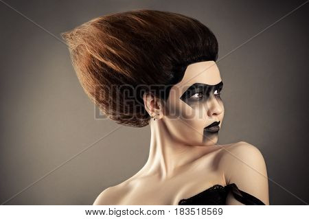 brunette woman with fashion hairstyle and creative dark makeup