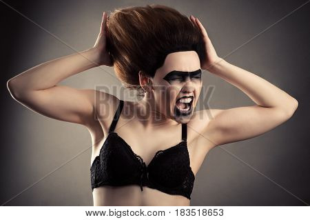 screaming woman with dark makeup and lush hair in bra