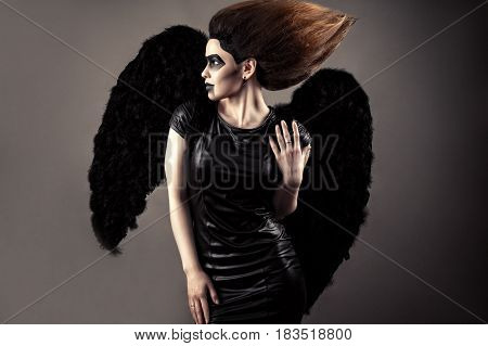 luxurious woman with lush hair and dark makeup with black wings