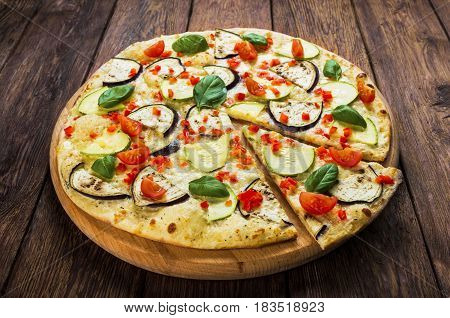 Delicious italian vegetarian pizza, with cherry tomatoes, peppers, aubergines and zucchini - thin pastry crust at wooden table background